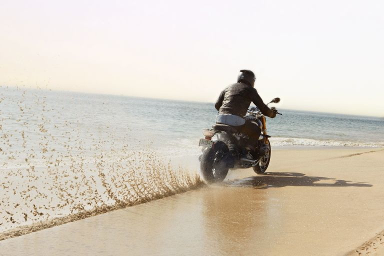 A BMW motorcyclist rides through the sand on the beach.